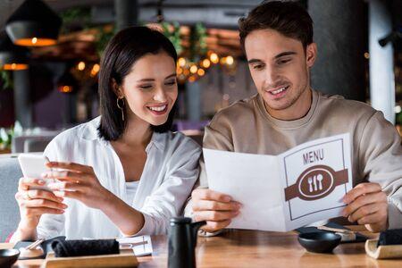 Photo pour happy woman holding smartphone near man with menu - image libre de droit