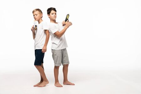 Foto de two brothers standing back to back, holding toy guns and looking at camera on white background - Imagen libre de derechos