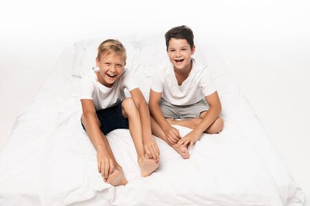 Photo for two happy brothers sitting on bed and smiling at camera on white background - Royalty Free Image