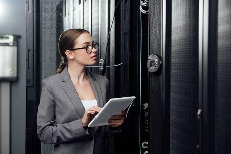 Photo pour selective focus of businesswoman in glasses holding digital tablet near server racks - image libre de droit