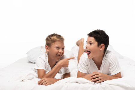 Photo pour cheerful boy pointing with finger at brother sticking out tongue isolated on white - image libre de droit