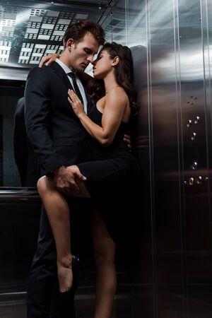 Photo pour young seductive couple hugging and flirting in lift - image libre de droit
