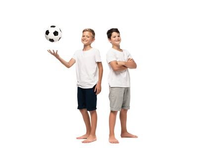 Photo for cheerful boy playing soccer ball near smiling brother standing with crossed arms on white background - Royalty Free Image
