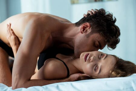 Foto de seductive man kissing passionate woman in bedroom - Imagen libre de derechos
