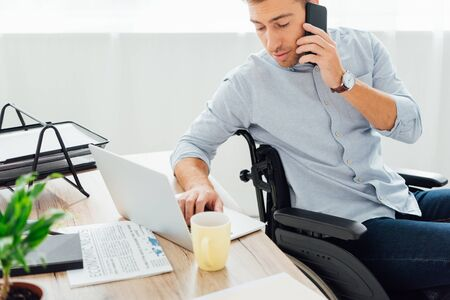 Photo for Man in wheelchair talking on smartphone and using laptop keyboard at desk - Royalty Free Image