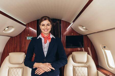 Photo pour smiling flight attendant in uniform looking at camera in private plane - image libre de droit