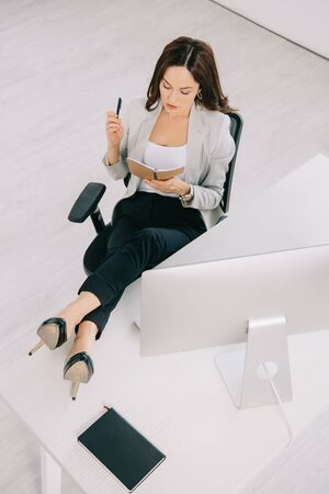 Photo pour high angle view of young, concentrated secretary looking at notebook while sitting at workplace - image libre de droit