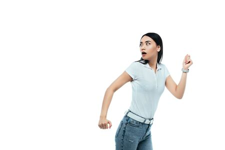 Foto de scared attractive asian girl running away isolated on white - Imagen libre de derechos