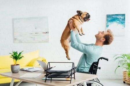 Foto de Smiling disabled man holding up french bulldog in living room - Imagen libre de derechos
