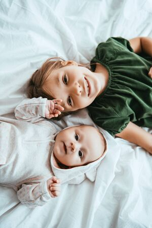 Photo pour top view of smiling child looking at camera while lying on white bedding near little sister - image libre de droit