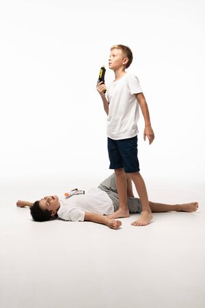 Photo pour boy blowing at toy gun near brother pretending dead on white background - image libre de droit