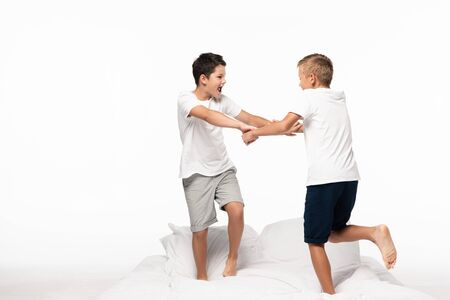 Photo for two brothers fighting for fun white standing on bed isolated on white - Royalty Free Image