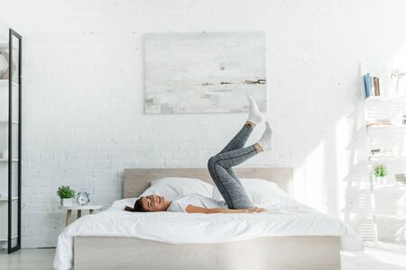 Foto de beautiful happy girl lying on bed in light bedroom - Imagen libre de derechos