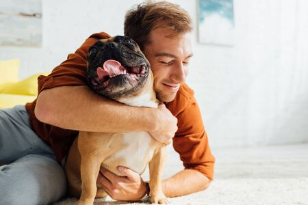 Foto de Smiling man hugging funny french bulldog on floor in living room - Imagen libre de derechos