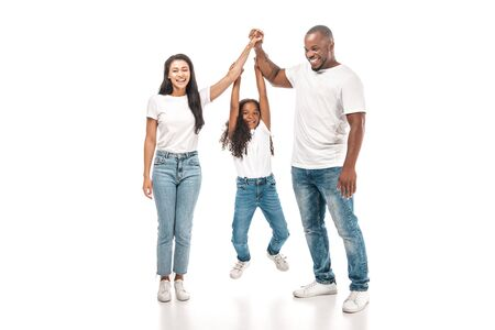 Photo pour cheerful african american child hanging on hands of parents on white background - image libre de droit