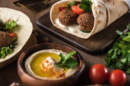 Photo pour selective focus of falafel with vegetables and sauce in pita near hummus on wooden table - image libre de droit