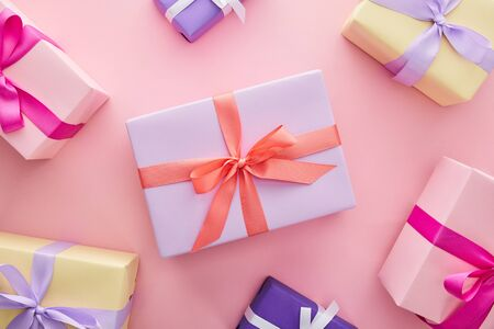 Photo for top view of colorful gift boxes with ribbons and bows on pink background - Royalty Free Image