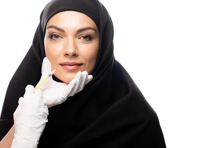 Photo pour young Muslim woman in hijab having beauty injection isolated on white, lip augmentation concept - image libre de droit