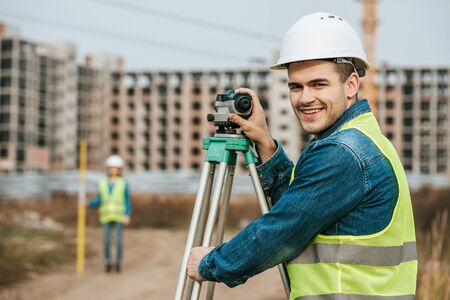 Photo pour Selective focus of smiling surveyor with digital level and colleague at background - image libre de droit