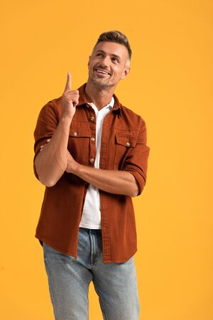 Foto de cheerful man pointing with finger and looking up isolated on orange - Imagen libre de derechos