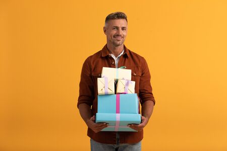 Photo for handsome man smiling while holding gift boxes isolated on orange - Royalty Free Image
