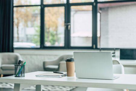 Foto de laptop, disposable cup, notebook and pen holder on white table in modern office - Imagen libre de derechos