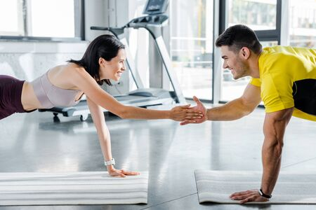 Photo pour smiling sportsman and sportswoman doing plank and clapping on fitness mats in sports center - image libre de droit
