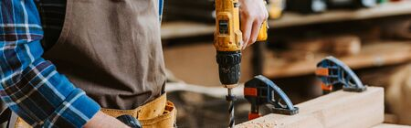 Photo pour panoramic shot of carpenter in apron holding hammer drill near wooden plank - image libre de droit