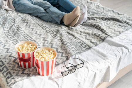 Photo for Cropped view of couple lying on bed beside popcorn buckets and 3d glasses - Royalty Free Image