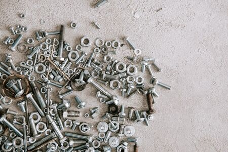 Photo for top view of metal screws and nails scattered on grey background - Royalty Free Image