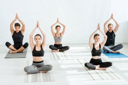 Photo for five young people meditating in half lotus pose with raised prayer hands - Royalty Free Image