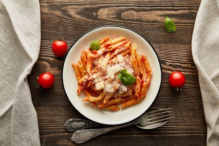 Photo pour top view of tasty bolognese pasta with tomato sauce and Parmesan in white plate near ingredients and cutlery on wooden table - image libre de droit