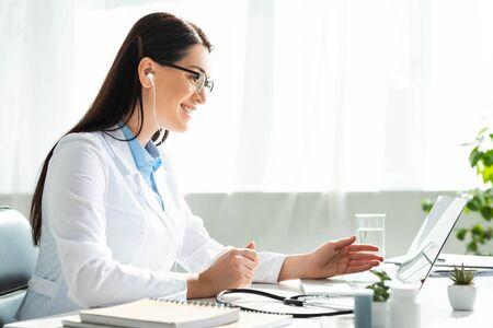 Foto de positive doctor in earphones having online consultation with patient on laptop in clinic office - Imagen libre de derechos