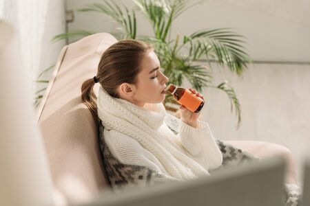Photo pour selective focus of sick girl sitting on sofa and drinking cough syrup - image libre de droit