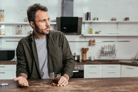 Photo pour Sad man holding whiskey glass and pills on kitchen table - image libre de droit