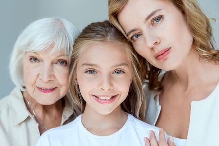 Photo pour mother, grandmother and smiling granddaughter looking at camera isolated on grey - image libre de droit