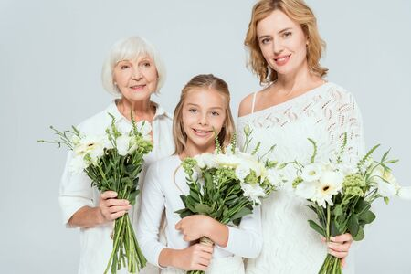Photo pour smiling granddaughter, mother and grandmother holding bouquets isolated on grey - image libre de droit