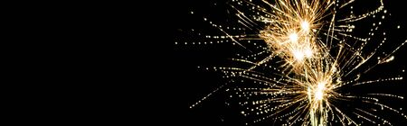 panoramic shot of yellow traditional fireworks in night sky, isolated on black
