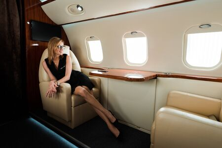 Photo pour cheerful businesswoman in glasses and dress looking at airplane window in private jet - image libre de droit