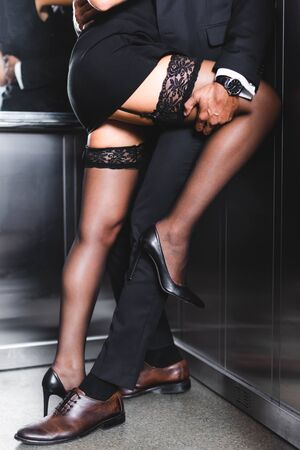Photo for Cropped view of businessman touching hip of woman in stockings in office elevator - Royalty Free Image
