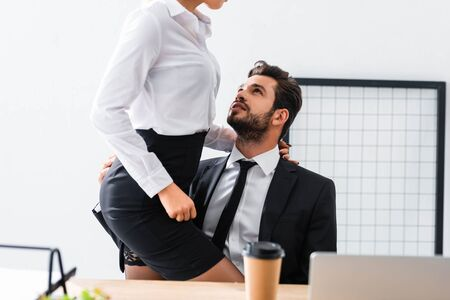 Photo pour Cropped view of businesswoman touching sexy businessman at workplace - image libre de droit