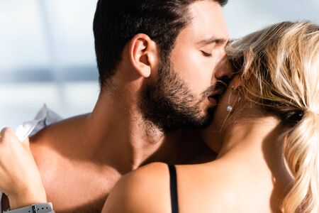 Photo for Shirtless businessman kissing blonde colleague - Royalty Free Image