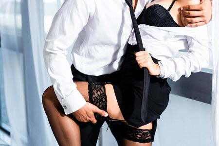 Photo pour Cropped view of sexy secretary in stockings pulling businessman tie - image libre de droit