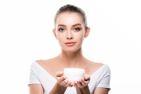 Photo pour attractive girl looking at camera while holding container with face cream isolated on white - image libre de droit