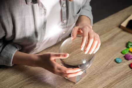 Photo for Cropped view of astrologer using crystal ball on wooden table - Royalty Free Image
