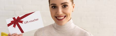 Photo pour Panoramic shot of smiling woman looking at camera and showing gift voucher - image libre de droit