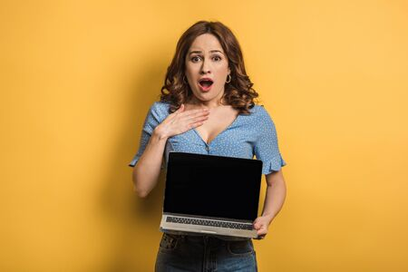 Photo pour shocked woman touching chest while holding laptop with blank screen on yellow background - image libre de droit