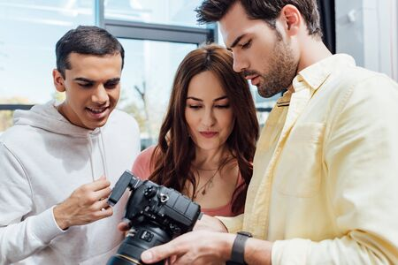 Photo pour attractive art director looking at digital camera near photographer and assistant - image libre de droit