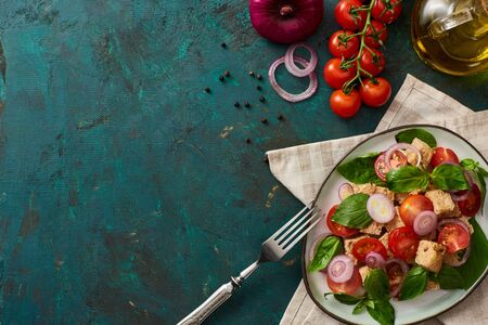 Foto für top view of delicious Italian vegetable salad panzanella served on plate on textured green surface with ingredients, napkin and fork - Lizenzfreies Bild