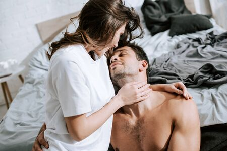 Photo for attractive girl looking at handsome muscular boyfriend in bedroom - Royalty Free Image